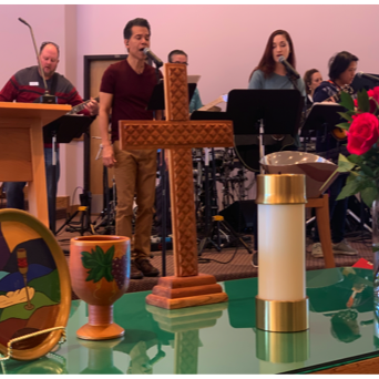 Praise band performing during worship with communion table in the foreground
